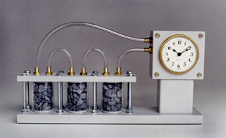 A clock with tubes connecting three recepticles holding stones